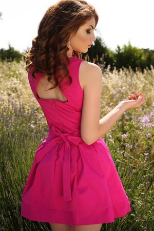 woman dress: fashion outdoor photo of beautiful young woman with dark hair in elegant pink dress posing in summer lavender field