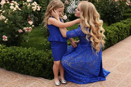 cabello rubio: como madre como hija. foto al aire libre de la hermosa mujer embarazada con el pelo largo y rubio en el cordón elegante vestido azul posando en el jardín de verano con su hija linda.
