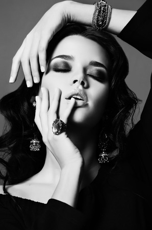 black and white fashion studio photo of beautiful sensual woman with dark hair and bright makeup,with bijou