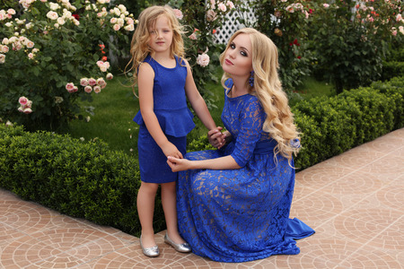 lace like: like mother like daughter. outdoor photo of beautiful pregnant woman with long blond hair in elegant lace blue dress posing in summer garden with her cute daughter.