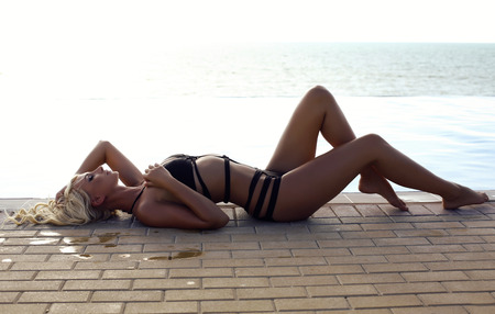 glamour nude: fashion outdoor photo of gorgeous sexy woman with blond hair in elegant swimsuit relaxing beside a  swimming pool