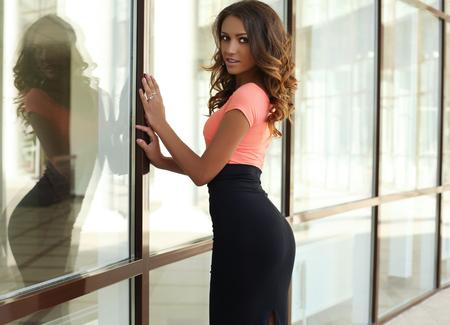 donne eleganti: all'aperto foto di moda di bella donna sensuale con i capelli scuri e il corpo abbronzato, indossando abiti eleganti, in posa accanto a finestra Archivio Fotografico