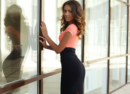 tanned body: fashion outdoor photo of beautiful sensual woman with dark hair and tanned body,wearing elegant clothes,posing beside window