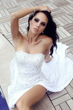 sensual woman: fashion outdoor photo of beautiful sensual woman with long dark hair in luxurious sequin dress posing in swimming pool Stock Photo