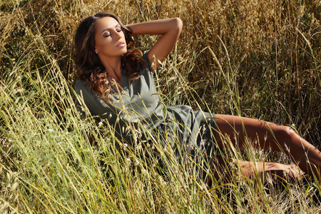 tanned body: fashion outdoor photo of beautiful sensual woman with dark hair and tanned body,wearing elegant clothes,posing in summer field