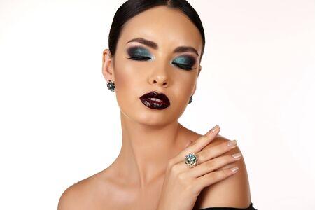 extravagant: fashion studio portrait of beautiful girl with dark hair with bright extravagant makeup and bijou Stock Photo