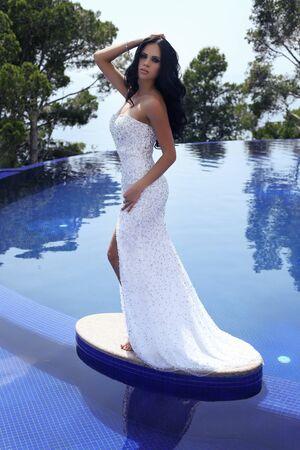 donne eleganti: all'aperto foto di moda di bella donna sensuale con lunghi capelli scuri in lussuoso abito di paillettes posa in piscina