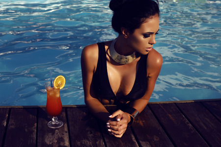 beach model: fashion outdoor photo of beautiful sensual woman with long dark hair in elegant black swimsuit relaxing in swimming pool with cocktail