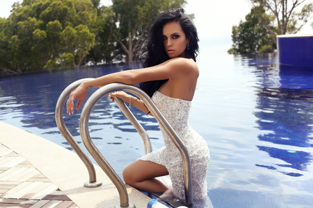 sexy dress: fashion outdoor photo of beautiful sensual woman with long dark hair in luxurious sequin dress posing in swimming pool Stock Photo