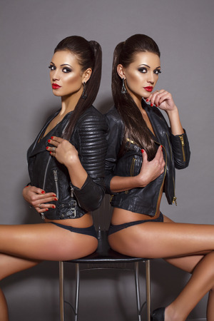 ni�as gemelas: moda foto de estudio de la mujer atractiva hermosa con el pelo y los labios rojos rectas oscuros, vestido con chaqueta de cuero,