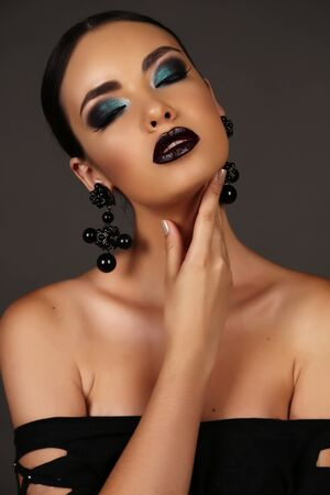 fashion studio portrait of beautiful girl with dark hair with bright extravagant makeup and bijou Stock Photo
