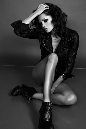 black and white fashion photo of beautiful sexy woman with luxurious curly hair in elegant jacket posing in studio