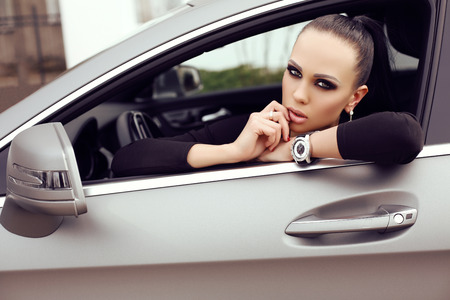 successful woman: fashion outdoor photo of sexy beautiful woman with dark hair in black elegant dress posing in luxurious auto Stock Photo