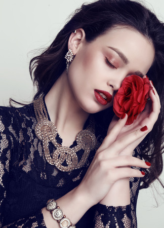 fashion studio photo of beautiful sensual woman with dark hair and bright makeup, holding flower in hands