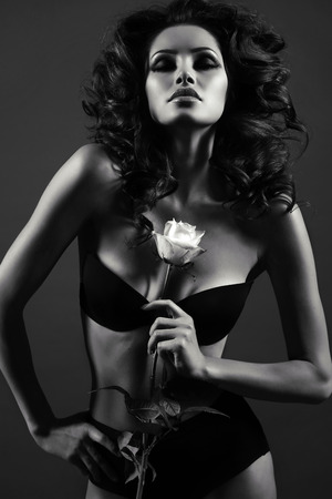 black: black and white fashion photo of beautiful sexy woman with luxurious curly hair in elegant lingerie posing in studio,holding rose in hands
