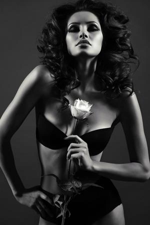 negro: Foto de la moda en blanco y negro de la mujer atractiva con el pelo rizado de lujo en elegante ropa interior que presenta en el estudio, la celebración de rosa en las manos