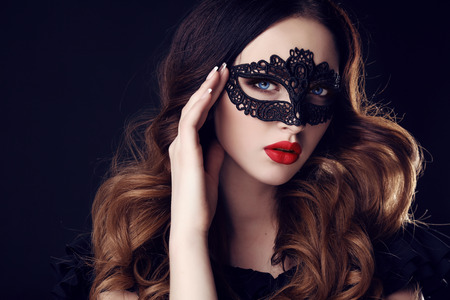 pretty hair: fashion photo of gorgeous woman with dark hair and blue eyes, with lace mask on her face,posing in dark studio