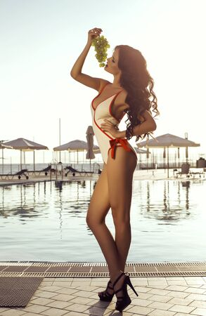 bunch of: fashion outdoor photo of beautiful sexy woman with dark hair in swimsuit posing with bunch of grapes beside swimming pool Stock Photo