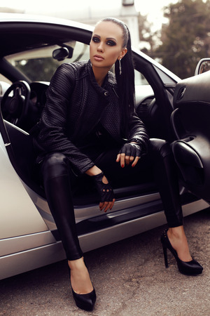 car accessory: fashion outdoor photo of sexy beautiful woman with dark hair in black leather clothes posing in luxurious auto