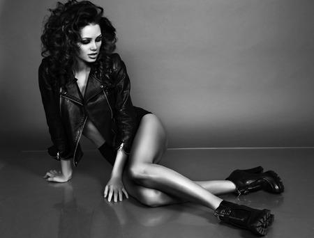 스튜디오에서 포즈 우아한 재킷에 고급스러운 곱슬 머리와 아름 다운 섹시 한 여자의 흑백 사진