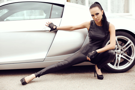 leather gloves: fashion outdoor photo of sexy beautiful woman with dark hair in black leather pants posing beside luxurious auto
