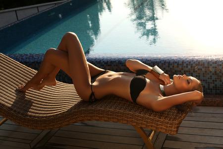 traje de bano: moda foto al aire libre de la hermosa chica sexy con el pelo rubio en un elegante traje de baño negro de relax en la silla de mimbre al lado de una piscina