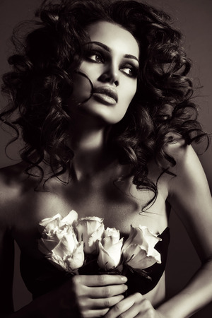 black and white fashion photo of beautiful sexy woman with luxurious curly hair in elegant lingerie posing in studio,holding roses in hands