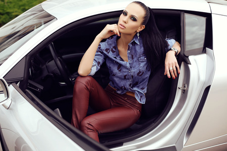 sexy woman car: fashion outdoor photo of sexy beautiful woman with dark hair in black leather pants and jeans shirt posing in luxurious auto Stock Photo