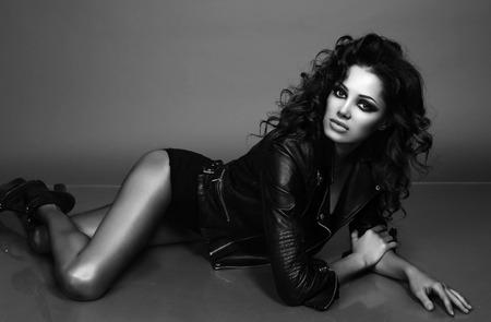 cabello rizado: Foto de la moda en blanco y negro de la mujer atractiva con el pelo rizado lujoso en el elegante chaqueta posando en el estudio Foto de archivo