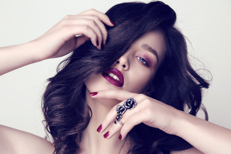 fashion studio photo of beautiful sensual woman with dark hair and bright makeup with bijou
