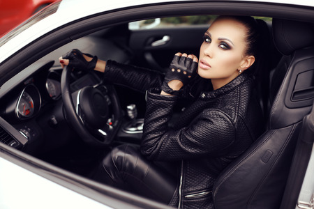 car accessory: fashion outdoor photo of sexy beautiful woman with dark hair in black leather jacket posing in luxurious auto