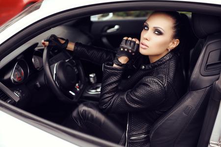 chaqueta: moda foto al aire libre de la mujer hermosa atractiva con el pelo oscuro en la presentación de la chaqueta de cuero negro en auto de lujo