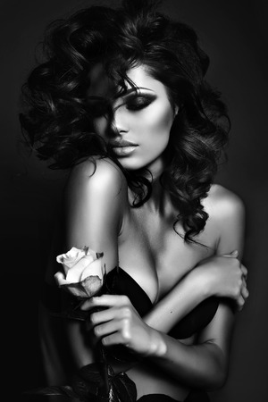modelo: Foto de la moda en blanco y negro de la mujer atractiva con el pelo rizado de lujo en elegante ropa interior que presenta en el estudio, la celebración de rosa en las manos