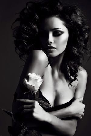 zwart en wit mode foto van mooie sexy vrouw met luxe krullend haar in elegante lingerie poseren in studio Stockfoto