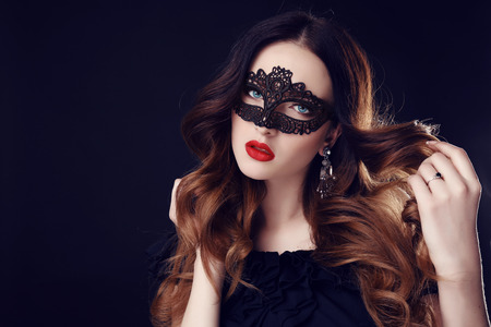 red lingerie: fashion photo of gorgeous woman with dark hair and blue eyes, with lace mask on her face,posing in dark studio