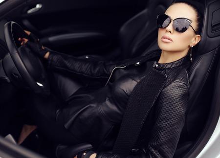 donna ricca: all'aperto foto di moda di sexy bella donna con i capelli scuri in giacca di pelle nera e occhiali da sole in posa in lussuosa auto