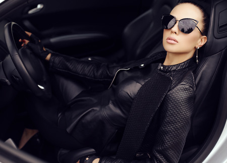 fashion outdoor photo of sexy beautiful woman with dark hair in black leather jacket and sunglasses posing in luxurious auto Foto de archivo