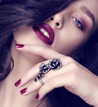 donne eleganti: studio fashion foto di bella donna sensuale con i capelli scuri e trucco luminoso con bijou