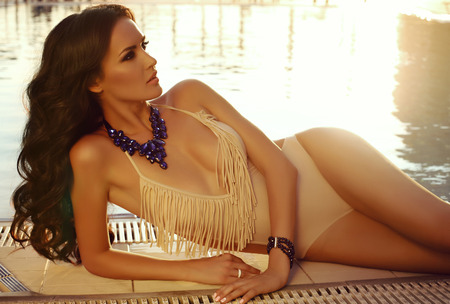 fashion outdoor photo of beautiful sexy woman with dark hair in elegant swimsuit and bijou posing beside swimming pool