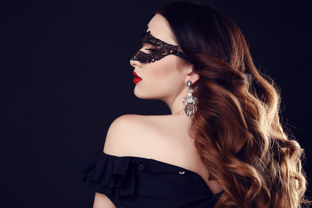 dark blue: fashion photo of gorgeous woman with dark hair and blue eyes, with lace mask on her face,posing in dark studio