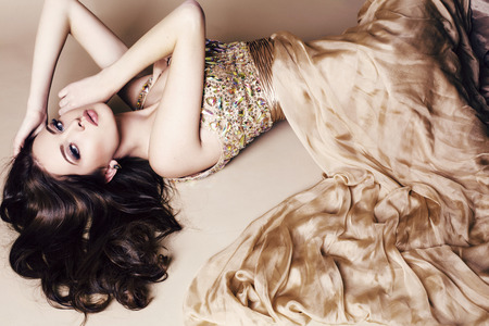 white dresses: fashion studio photo of beautiful young woman with long dark hair wearing luxurious sequin dress