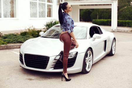 donna ricca: all'aperto foto di moda di sexy bella donna con i capelli scuri in pantaloni di pelle nera e jeans camicia in posa accanto a lussuosa auto