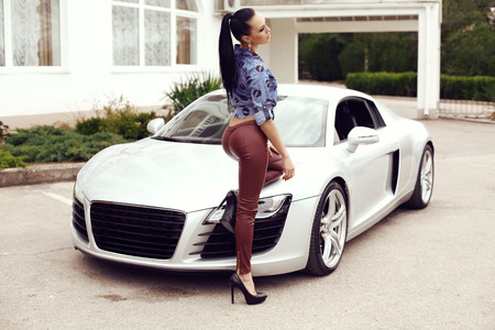 fashion outdoor photo of beautiful woman with dark hair in black leather pants and jeans shirt posing beside luxurious auto