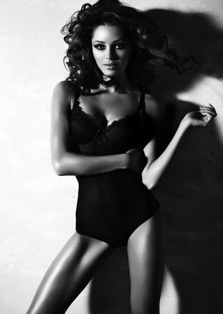 brunette lingerie: black and white fashion photo of beautiful sexy woman with luxurious curly hair in elegant lingerie posing in studio