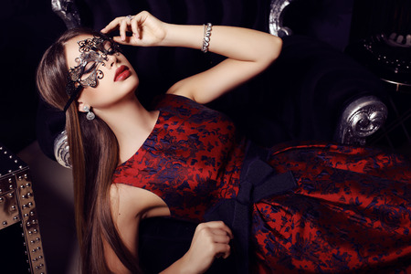luxurious: fashion photo of gorgeous woman with dark hair  in elegant dress and mask on face posing in luxurious interior Stock Photo