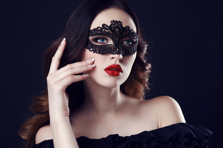 Mode foto van prachtige vrouw met donker haar en blauwe ogen, met kant masker op haar gezicht, poseren in een donkere studio