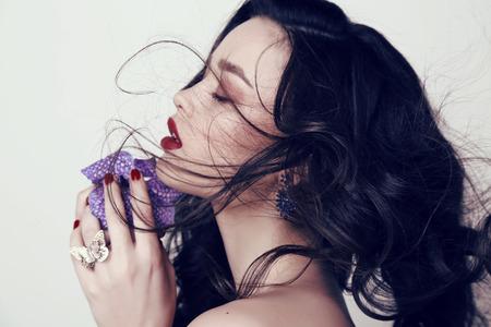 fashion studio foto van mooie sensuele vrouw met donker haar en lichte make-up, orchideebloem in handen te houden