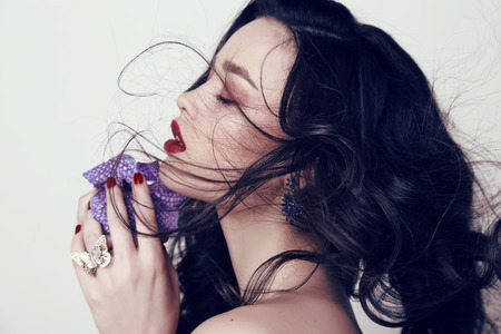 fashion studio photo of beautiful sensual woman with dark hair and bright makeup, holding orchid flower in hands Zdjęcie Seryjne