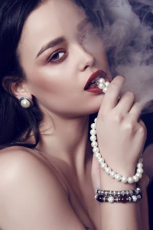 mujeres elegantes: estudio de moda foto de la hermosa mujer sensual con el pelo oscuro y maquillaje brillante con bijou, posando en el humo del cigarrillo