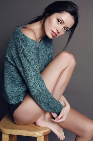chica sexy: estudio de moda foto de la hermosa mujer sensual con el pelo oscuro y piel brillo saludable, vestido con chaqueta de punto acogedor